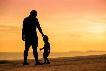 Silhouette father and son on beach in sunset time with twilight sky