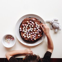 Overhead picture of a boy decorating a cake with chocolate eggs.
