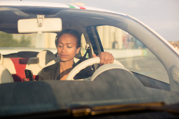 Young black businesswoman texting in car