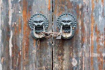 Old chinese traditional wooden gate with Lion door knockers and a chain