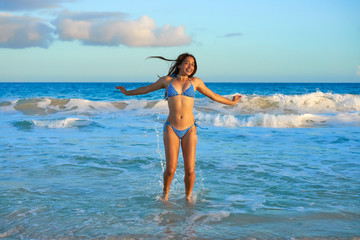 Latin bikini girl jumping in Caribbean beach
