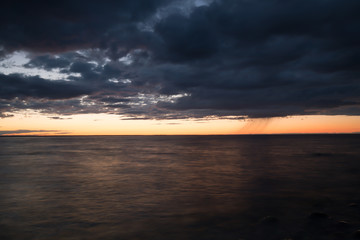 Sunset over the swedish southern coast with rainclouds and rain on the horizon