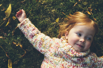 Happy three year old girl laying on grass with autumn leaves