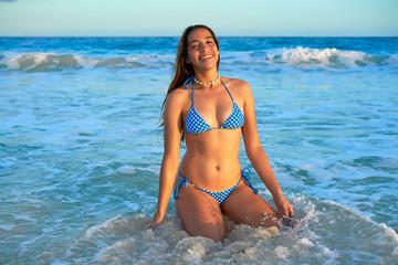 Latin bikini girl happy sitting in Caribbean