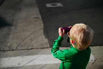 child taking photo with camera