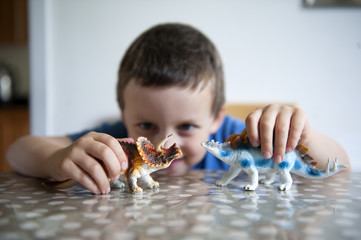 young boy playing with toy dinosaurs