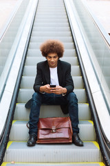 Young afro american businessman sending text message on his mobile phone sitting on an escalator.