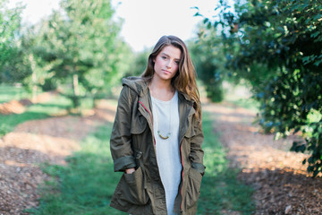 Beautiful young woman in a jacket standing outside