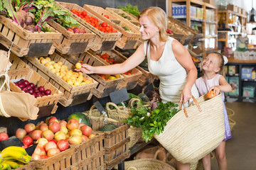 Mother with daughter shopping fruits