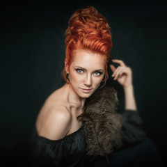 Portrait of redhead woman with blue eyes wearing black dress on dark background. Girl doesn't look into the camera. Female is posing with bird feather.
