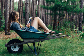 Woman Reading in a Wheelbarrow in a Forest
