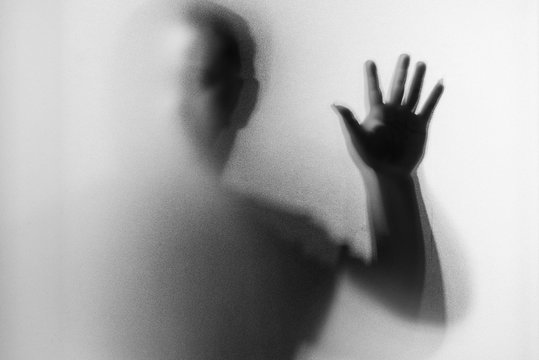 Shadow blur of horror man.Dangerous man behind the frosted glass.Mystery man.Black and white picture.Blur picture.Add effects noise and grain.Halloween.Halloween.