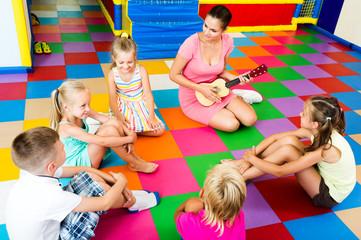 Kids sitting around teacher with small guitar