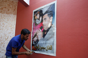 A man attaches a picture of a local singer at a musical instruments shop in east Mosul