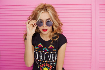 Fun and colorful.  Close up portrait of Young pretty happy blonde woman in shorts and sunglasses posing against pink background. Beauty and fashion concept.
