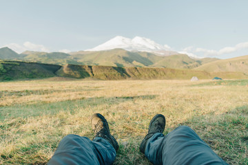 Man sitting in front of mountain Elbrus.