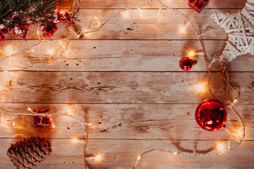 top view of Christmas and new year decorations on wooden desk with lights and free space for your text