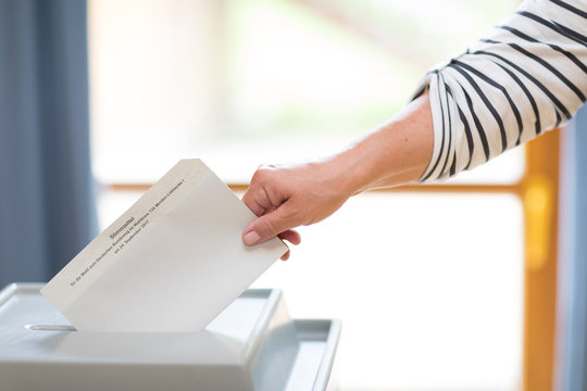 Stimmzettel wird in Wahlurne geworfen