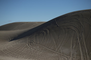 Sand dunes in the desert with tire tracks