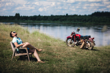A young handsome man relaxes in an armchair against the background of a river and an old motorcycle. The concept of relaxation from modern gadgets.