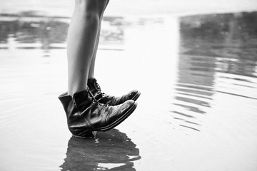 Legs in Black Boots in Calm Puddle