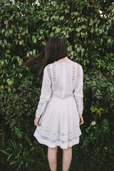Girl in a white, vintage dress facing backwards