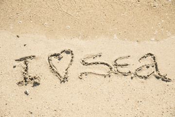 The inscription on the sand near the sea and the waves - I love sea. Background.