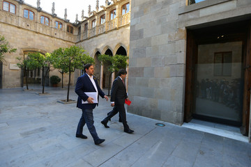 Catalan President Puigdemont walks with Vice President Junqueras as they arrive to hold a cabinet meeting at Generalitat Palace in Barcelona