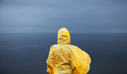 Woman in yellow raincoat looking away on deep blue sea in rainy autumn day.