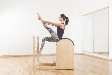Beautiful woman performing pilates exercise, training on barrel equipment