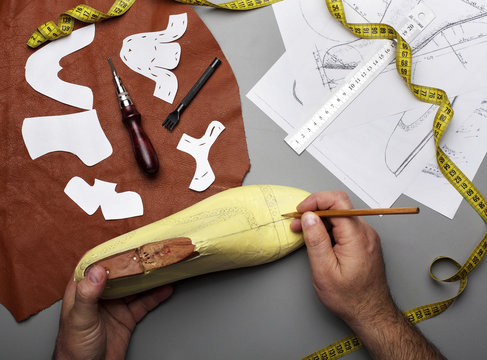 Modelling design of a shoes.Workplace of shoe designer.Hands of designer draw a shoe design .Copy space