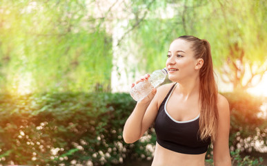 Beautiful, fitness sport girl with ponytail drinks water in the summer green park. Girl drinks water after sport
