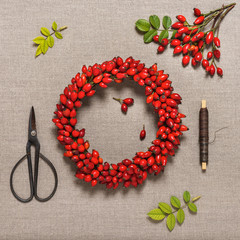 Traditional christmas holiday door wreath with wild rose fruits. Decorative autumn homemade concept. Step 3. Top view.