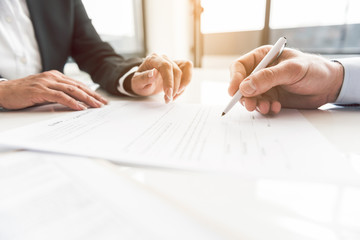 Male hand signing contract at desk