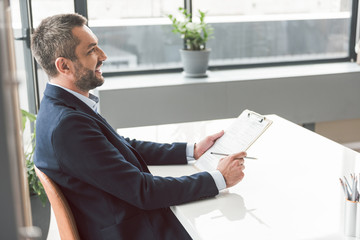 Outgoing businessman write paper at table