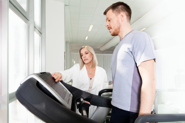 athlete on the treadmill he performs the instructions of physical therapist who assists him