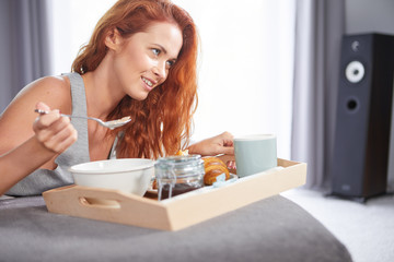 Beautiful happy redhead woman having breakfast in bed
