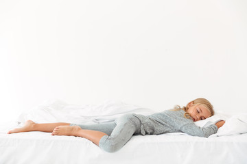 Full length portrait of sleeping peaceful girl in gray pajamas lying in bed
