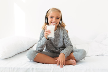 Pretty little girl in headphones holding glass of milk, sitting in bed, looking at camera