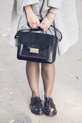Woman legs wearing black shoes on the street