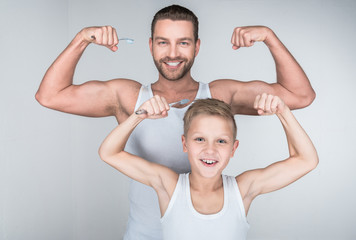 father and son showing biceps