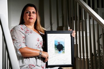 Farrah Fasold poses for a portrait with a painting of her late father Harold Dillard at her home in Flower Mound