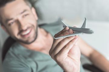 Joyful guy is holding little aircraft