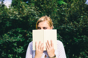 Young blond woman holding a book in the park