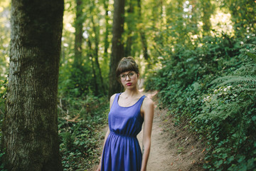 Girl Standing in the Forest with a Blue Dress