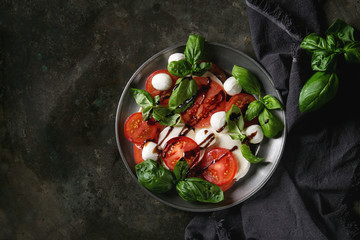 Italian caprese salad with sliced tomatoes, mozzarella cheese, basil, olive oil. Served in vintage metal plate on textile napkin over dark metal background. Top view with space. Rustic style