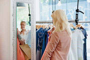 Woman looking at a dress in the mirror while shopping
