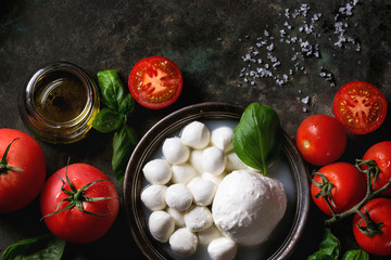 Ingredients for italian caprese salad. Mozzarella balls, buffalo in metal vintage plate, tomatoes, basil leaves, olive oil with vinegar over dark background. Top view with space. Rustic style