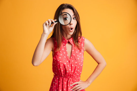 Close-up portrait of surprised beautiful woman looking at camera through magnifying glass