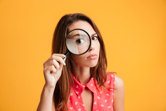 Close-up portrait of young serious woman looking through a magnifying glass